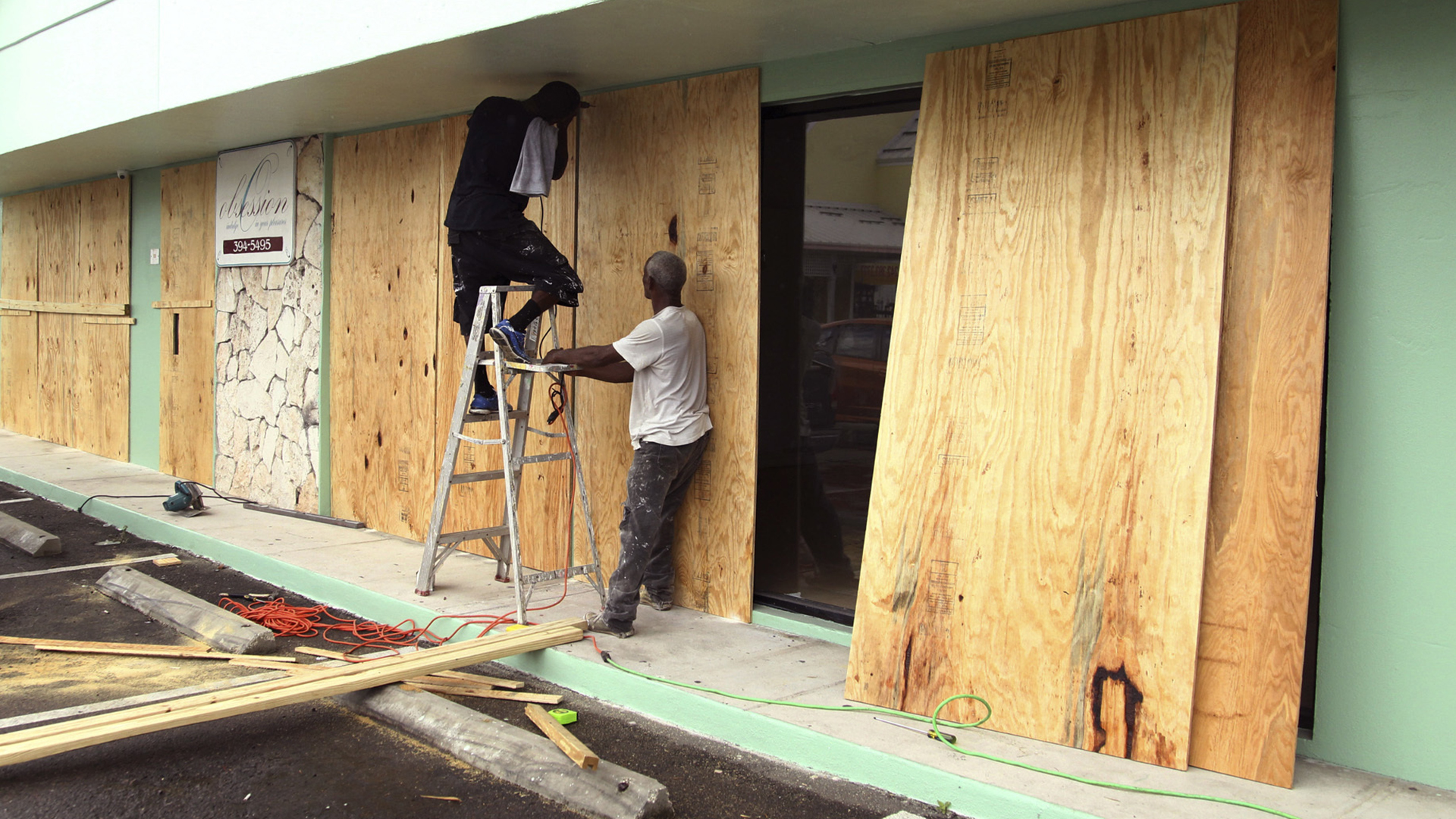 Charles Charry, on ladder, and Colin Dean secure plywood over the windows of Obsession Design clothing store in preparation for the arrival of Hurricane Matthew in Nassau, Bahamas, Wednesday, Oct. 5, 2016. Forecasters said the storm was on track to roll directly over the capital city before nearing the Florida coast. (AP Photo/Tim Aylen)